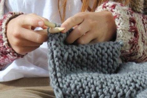 Manos de niña tejiendo